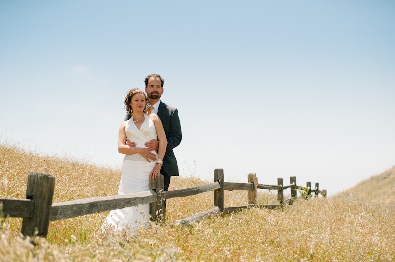 Bride and Groom standing at rustic wooden fence in Marin