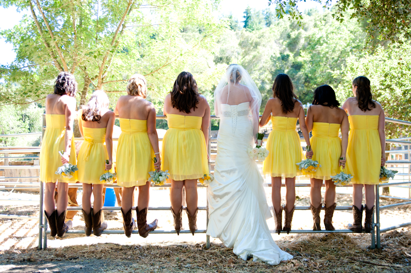 Bride and bridesmaids standing on horse corral