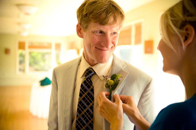 Bride applying boutonniere to Groom's lapele