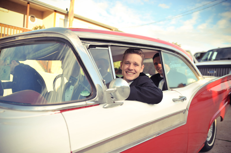 Smiling groom in vintage Ford Fairlane at San Diego Destination wedding