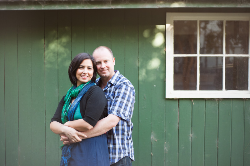 Couple in front of rustic green wood wall in San Francisco