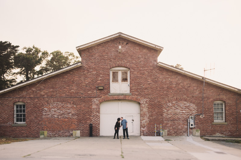 Wide frame photo of engaged couple kissing with rustic building