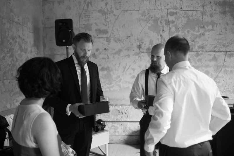 Groom exchanging gifts with groomsmen