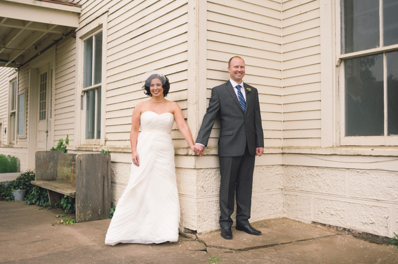 Bride and Groom holding hands around corner during First Look