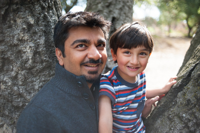 Portrait of father with son climbing in tree in Oakland, CA