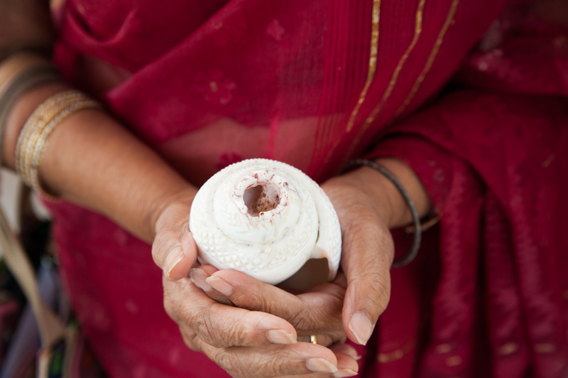 Detail of woman holding conch shell during Bengali ceremony