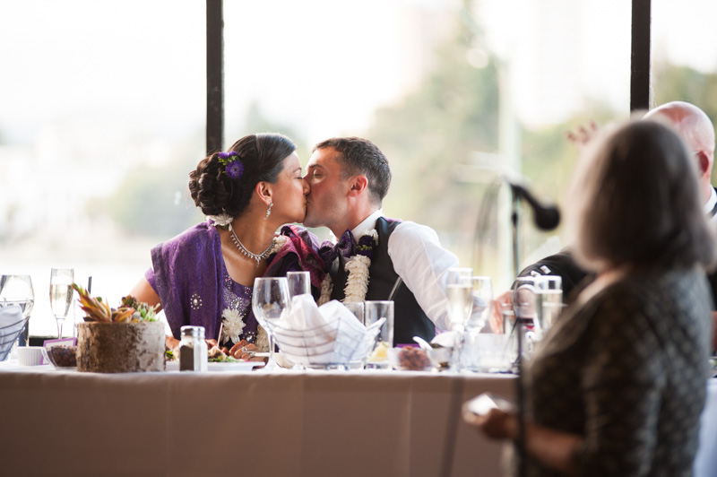 Bride and Groom kiss during wedding reception in Oakland