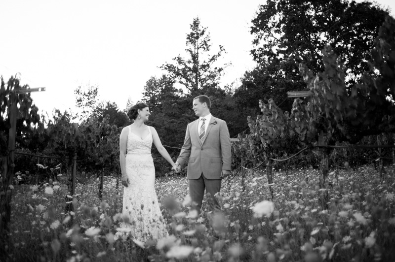 Black and white of bride and groom holding hands in wine country field