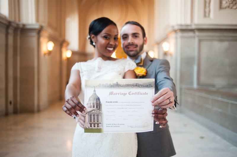 Bride and Groom holding marriage certificate in San Francisco at City Hall