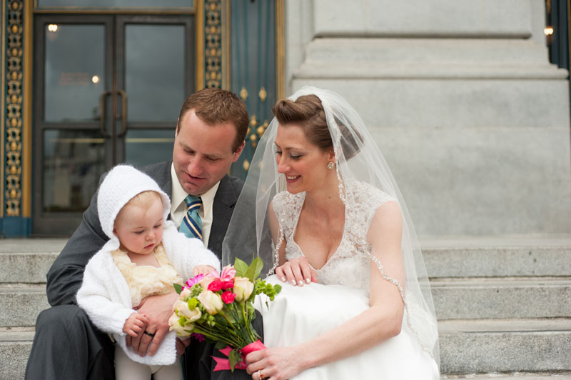 Bride and Groom on the steps of San Francisco with their daughter