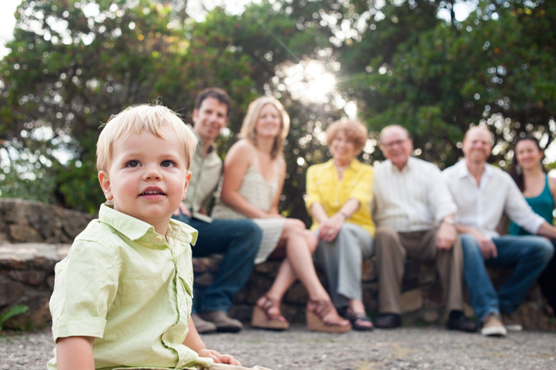Young child sitting in front of family members