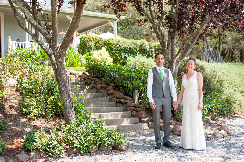 Couple standing in front of home on their wedding day in Sebastopol