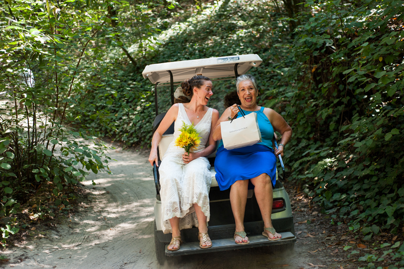 Bride and mother in law riding in golf cart on wedding day