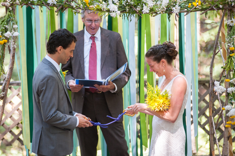 Bride and Groom exchanging rings attached to carabiners