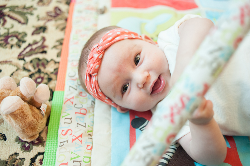 Baby girl playing on play mat