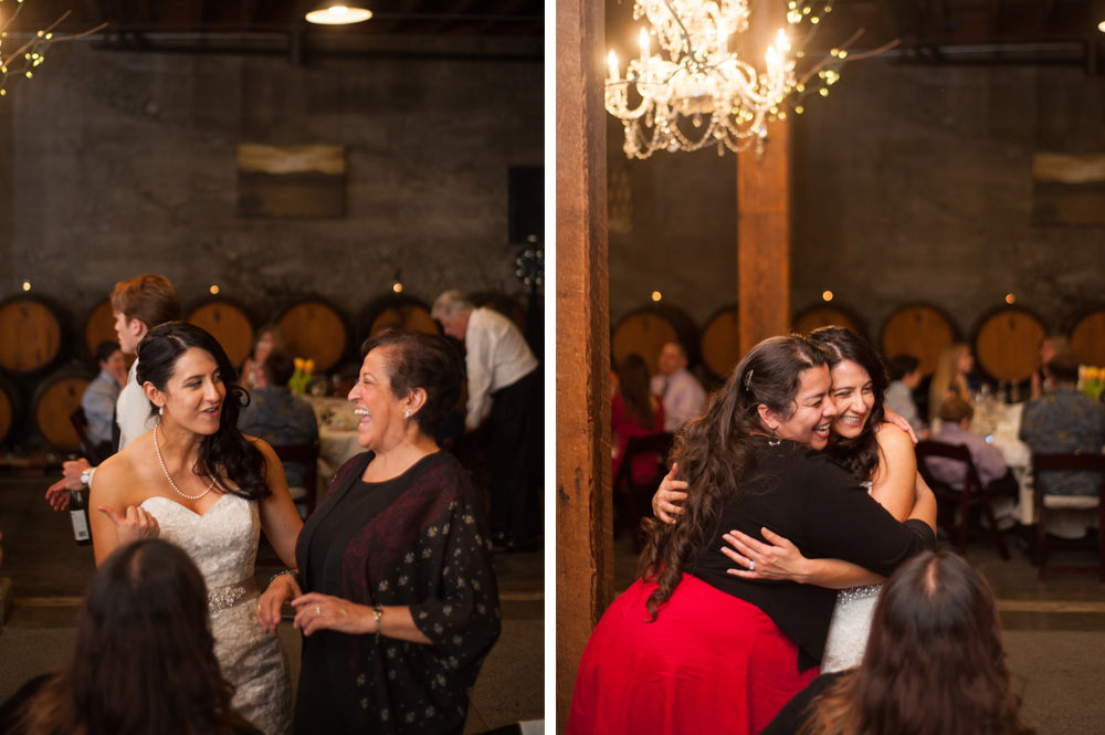 Candid of bride with wedding guests inside wine cellar