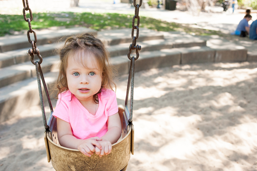 Portrait of young girl in swing at Piedmont Park during family photo sesison