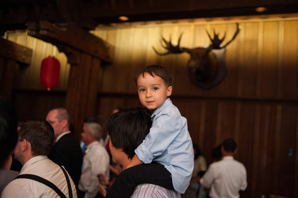 Candid photo of kid up on parents shoulders
