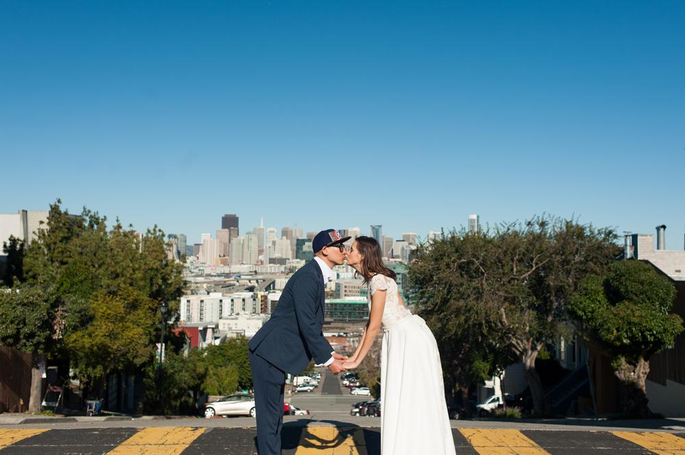 Bride and Groom kiss in crosswalk with San Francisco skyline behind them