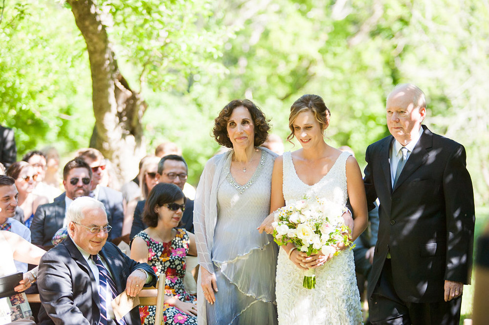 Bride walking down the aisle with parents during ceremony at Dawn Ranch