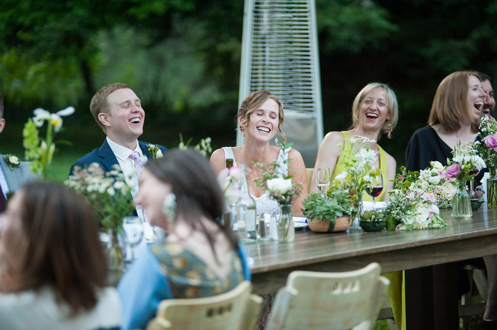 Candid photo of bride and groom laughing during dinner at their wedding at Dawn Ranch