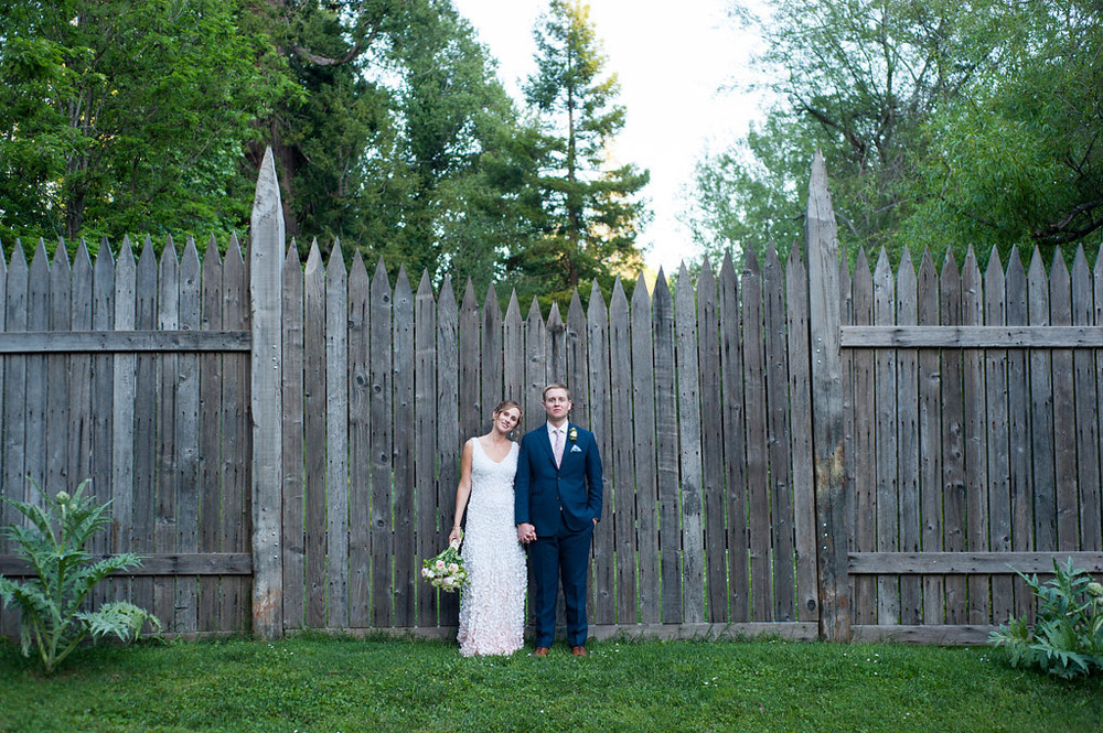 Portrait of bride and groom in front of rustic wood mideviel wall