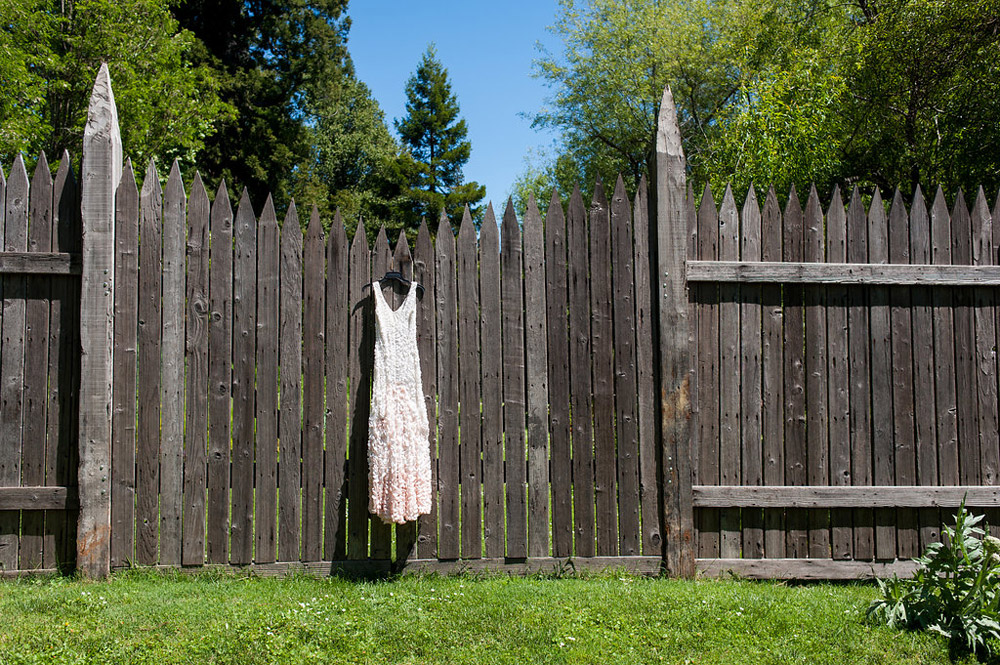 Wedding dress hanging on wooden fence at Dawn Ranch