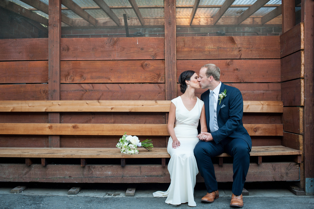 Bride and groom kissing in temescal alley