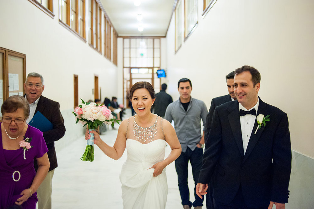 Candid portrait of bride and groom walking to City Hall wedding ceremony