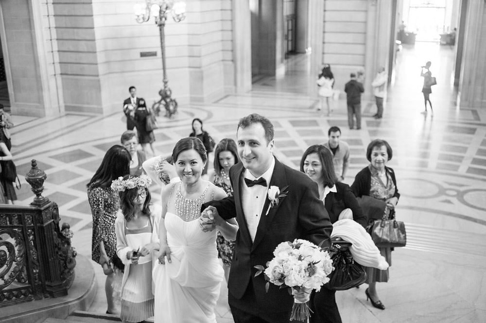 Black and white photo of bride and groom climbing grand staircase at San Francisco City Hall