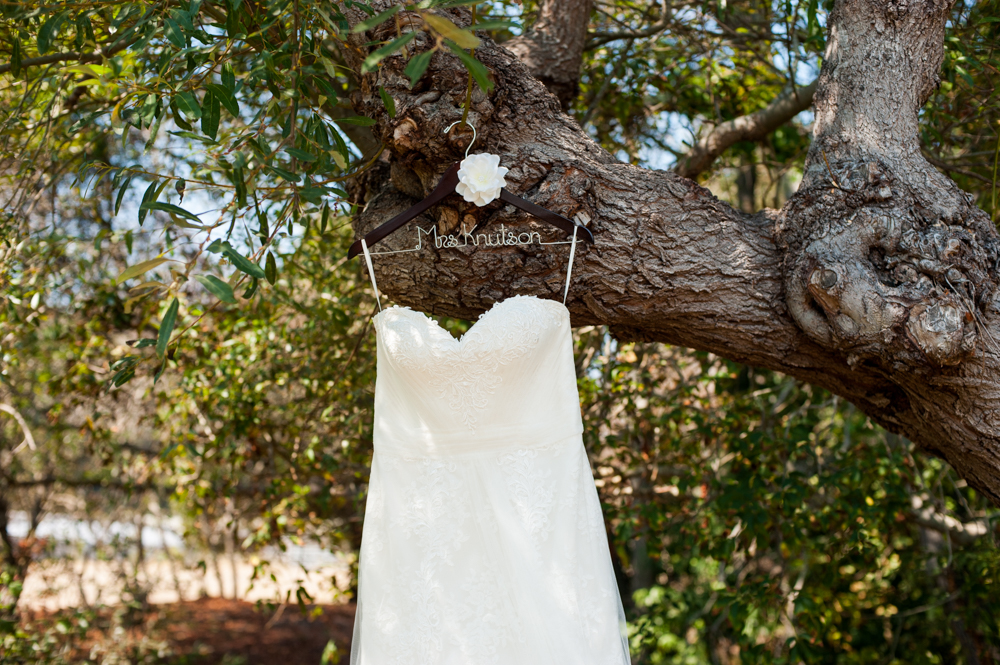 Detail of wedding dress hanging in tree with custom hanger