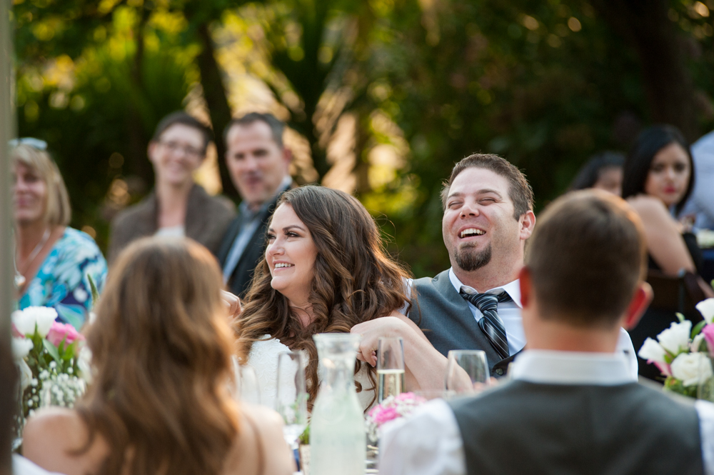 Candid portrait of bride and groom listening to toasts at Rancho Soquel