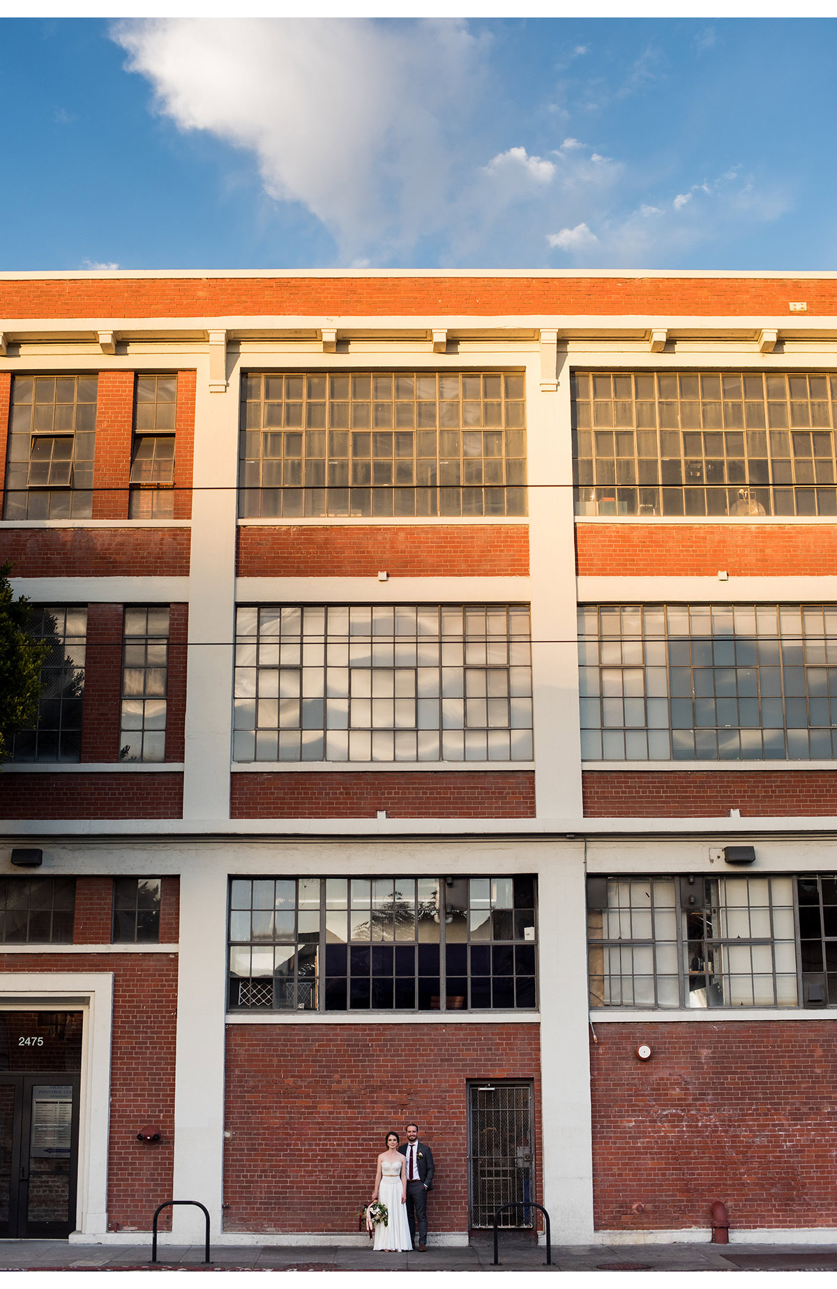 Large brick building with tiny bride and groom in San Francisco
