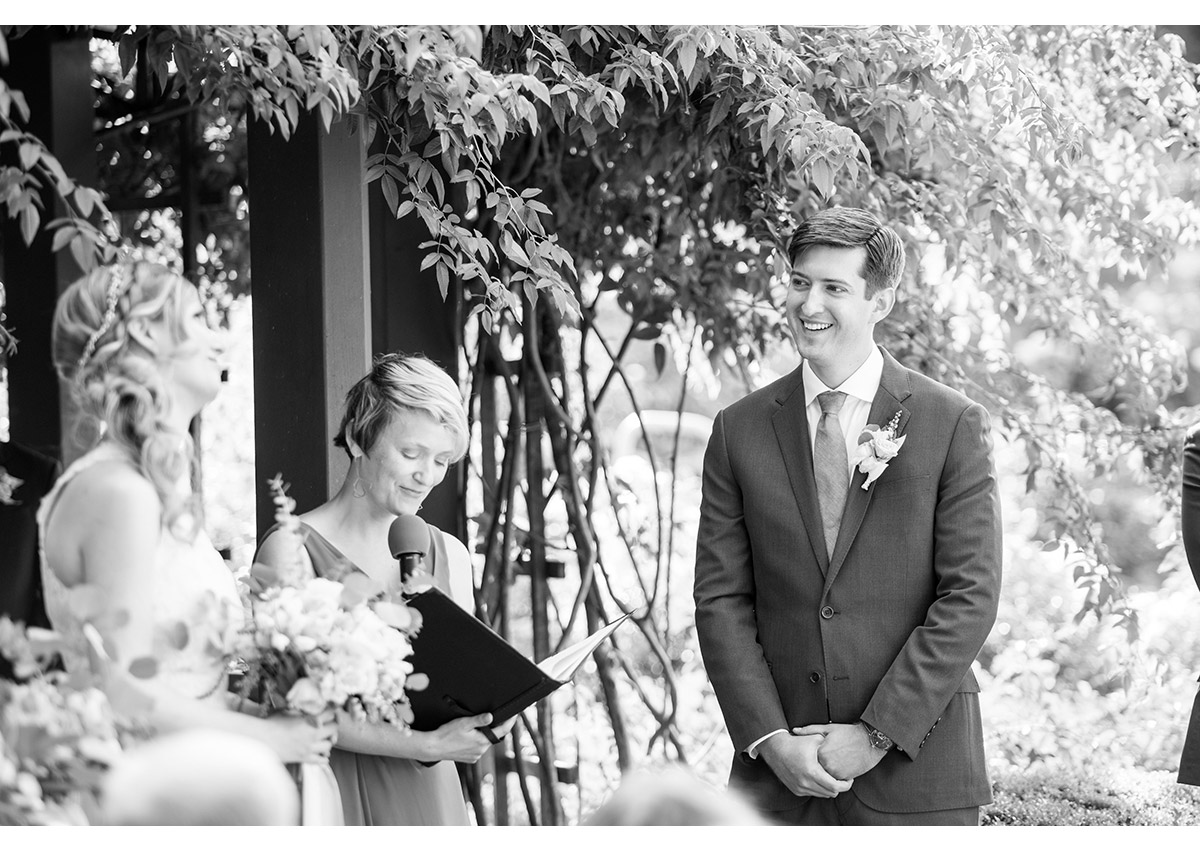 Black and white photo of groom smiling at his bride during wedding ceremony