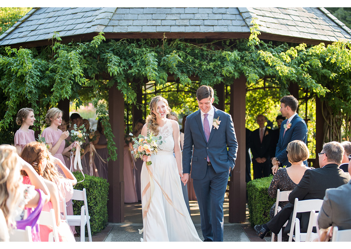 Happy bride and groom walking down aisle after wedding ceremony at Heather Farm gardens