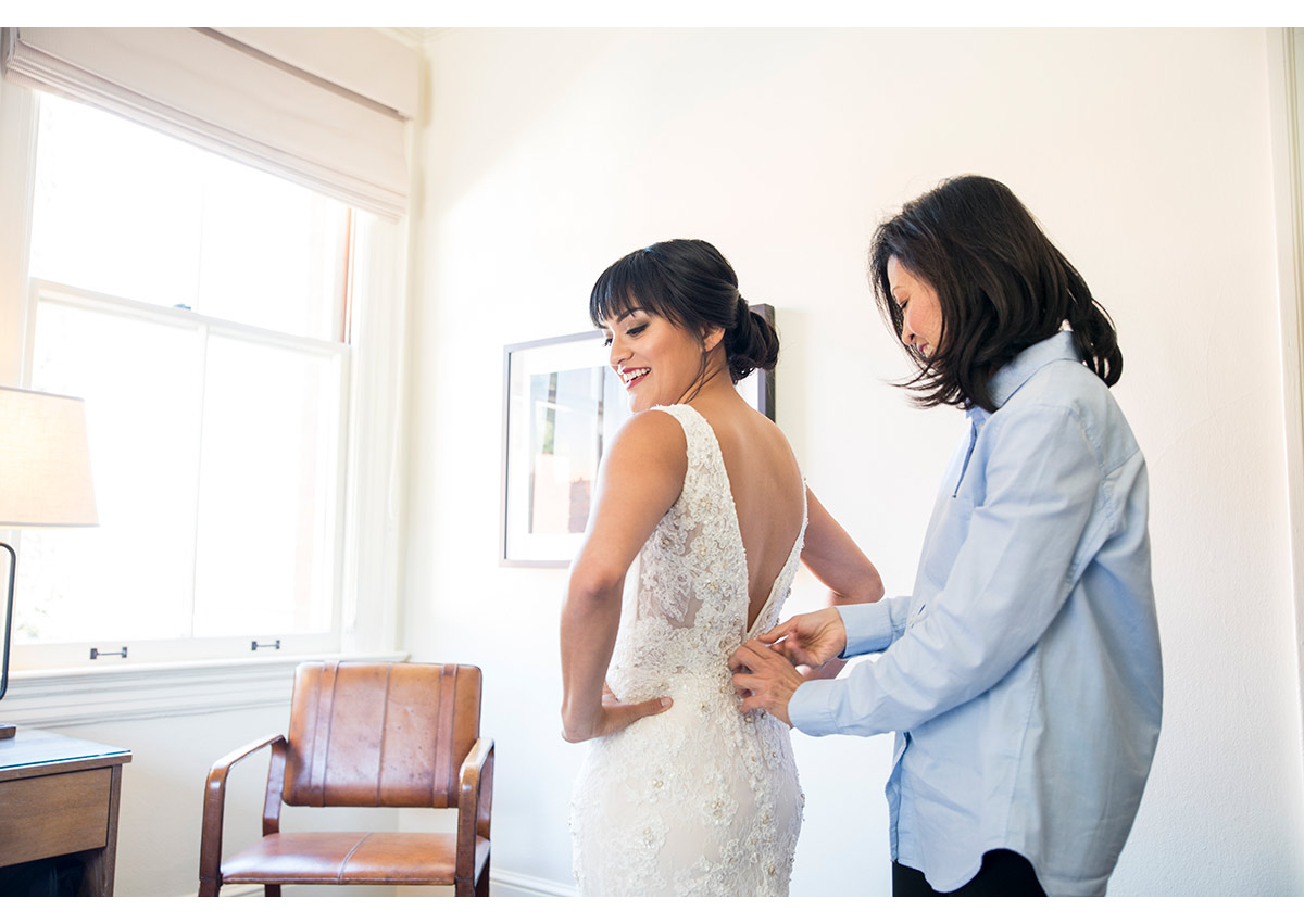 Mother of bride helping bride into wedding dress at Inn at the Presidio