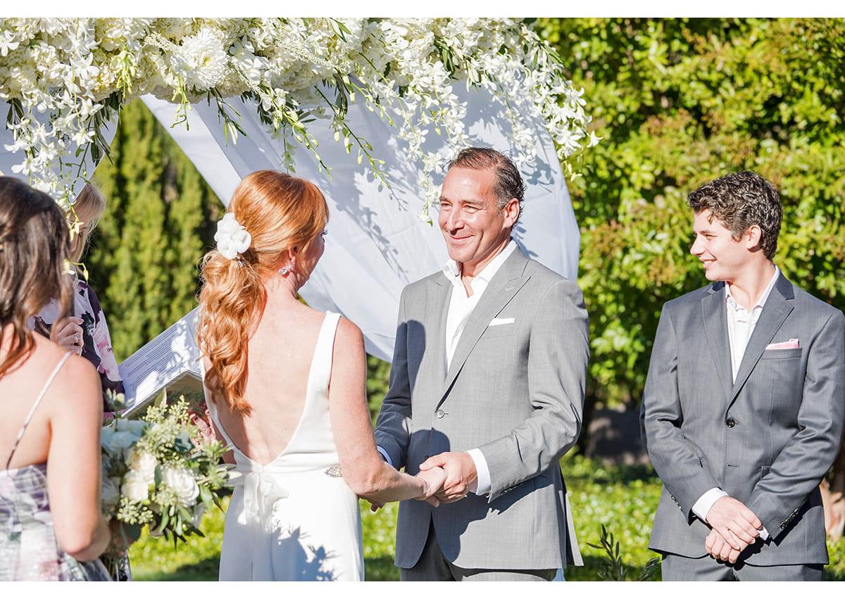 Groom holding Brides hands during wedding ceremony