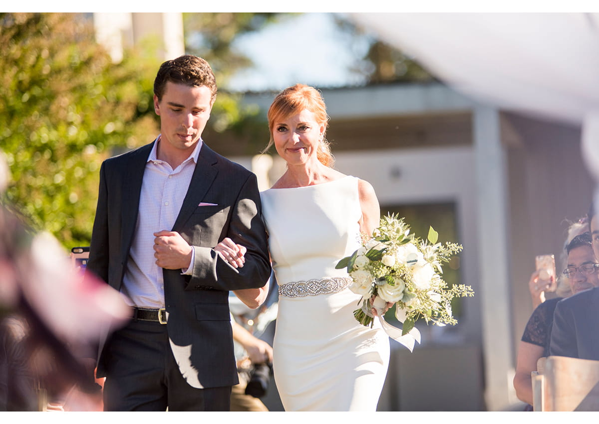 Bride walking down aisle with step son