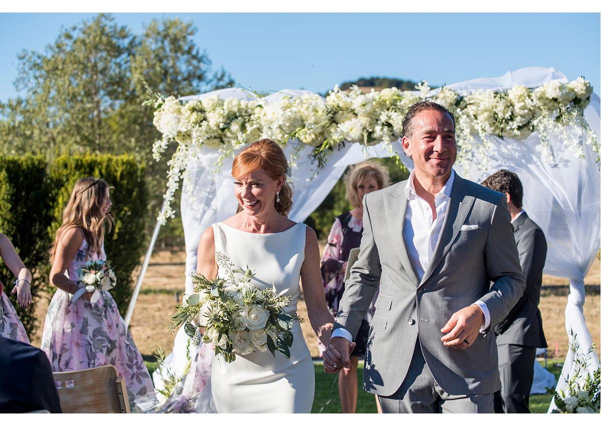 Bride and Groom walking down aisle smiling