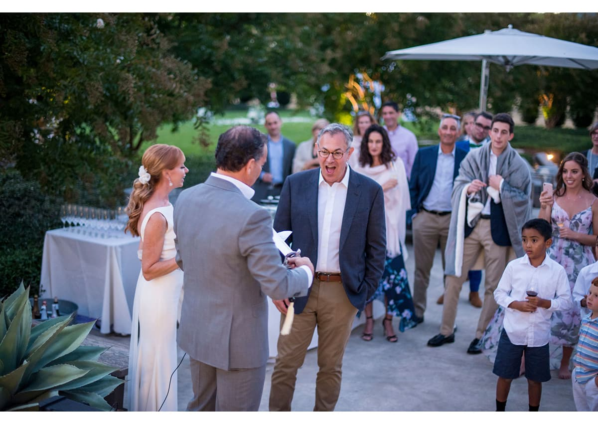Bride and Groom presenting host with champagne saber