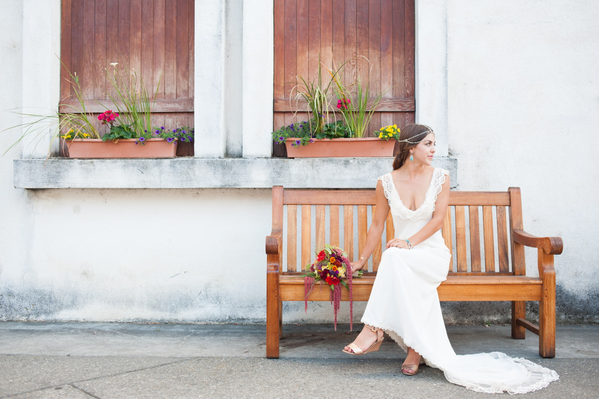 Bride sits on bench at Wente Vineyards