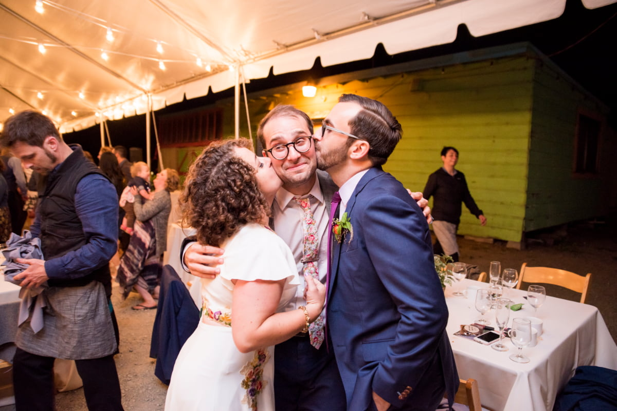 Bride and Groom kissing officiant on the cheeks