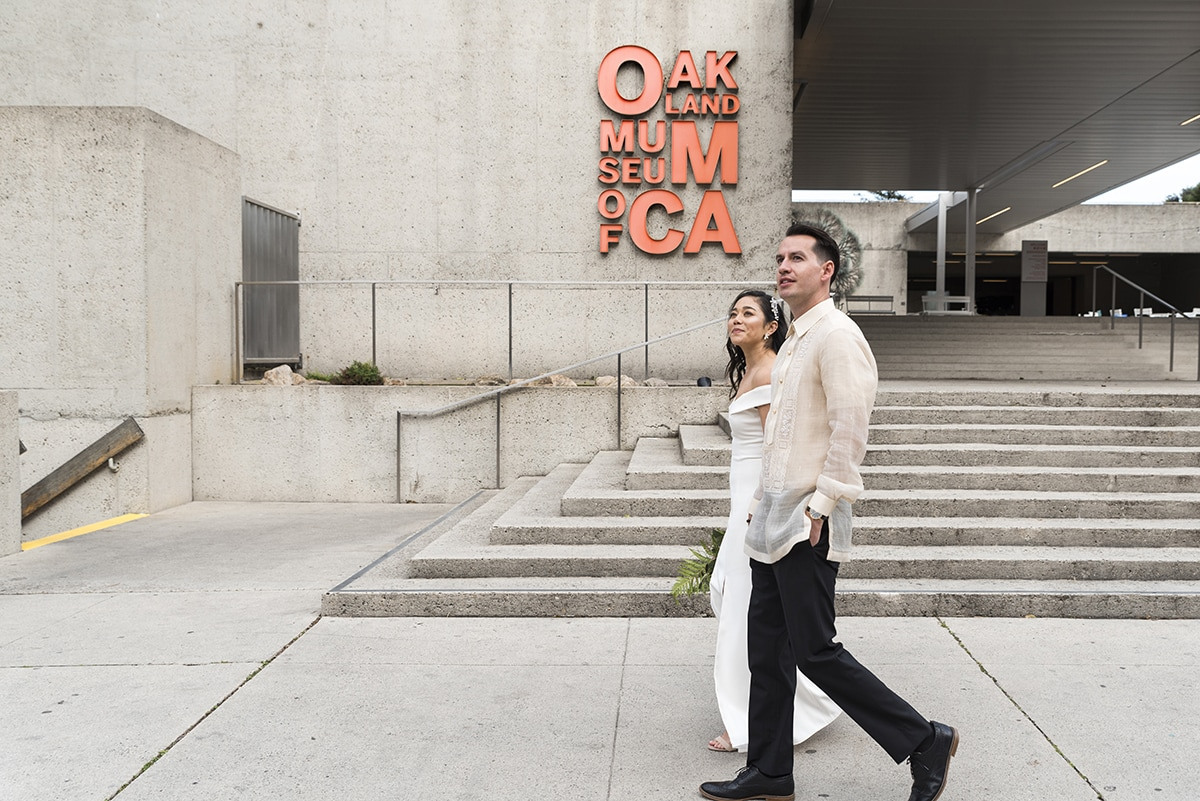 Bride and Groom walking with Oakland Museum in background