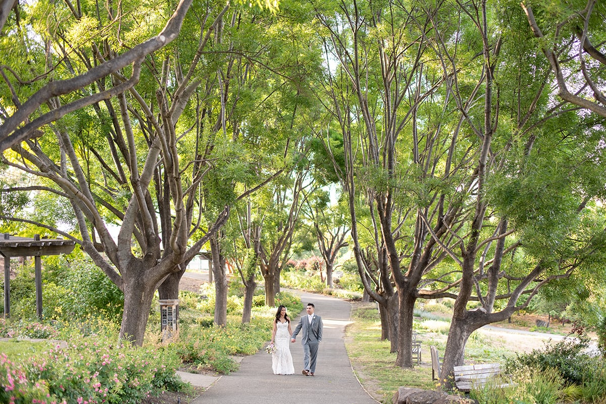 Bride and Groom walking along tree lined path at Heather Farm in Walnut Creek