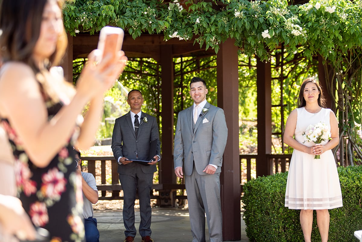 Groom watching Bride walk down wedding aisle