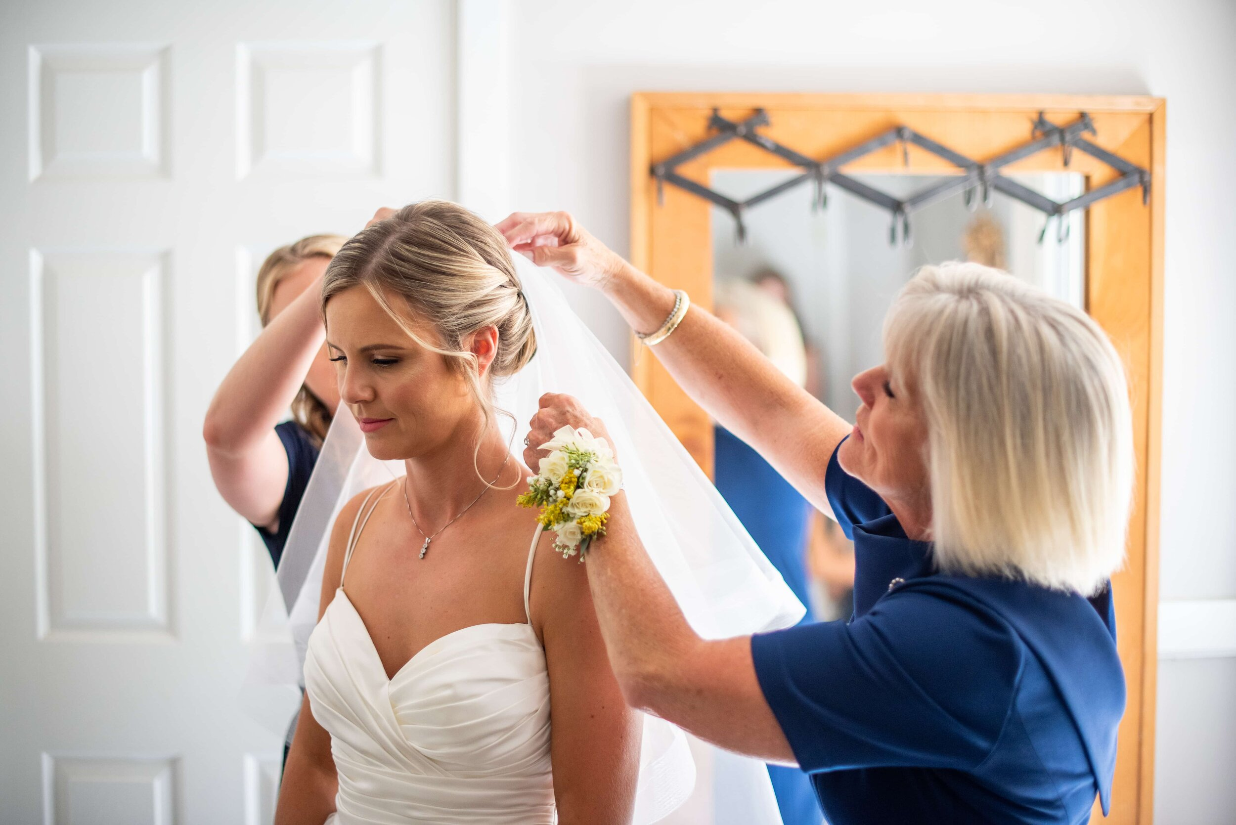 Mother of bride helping daughter with veil