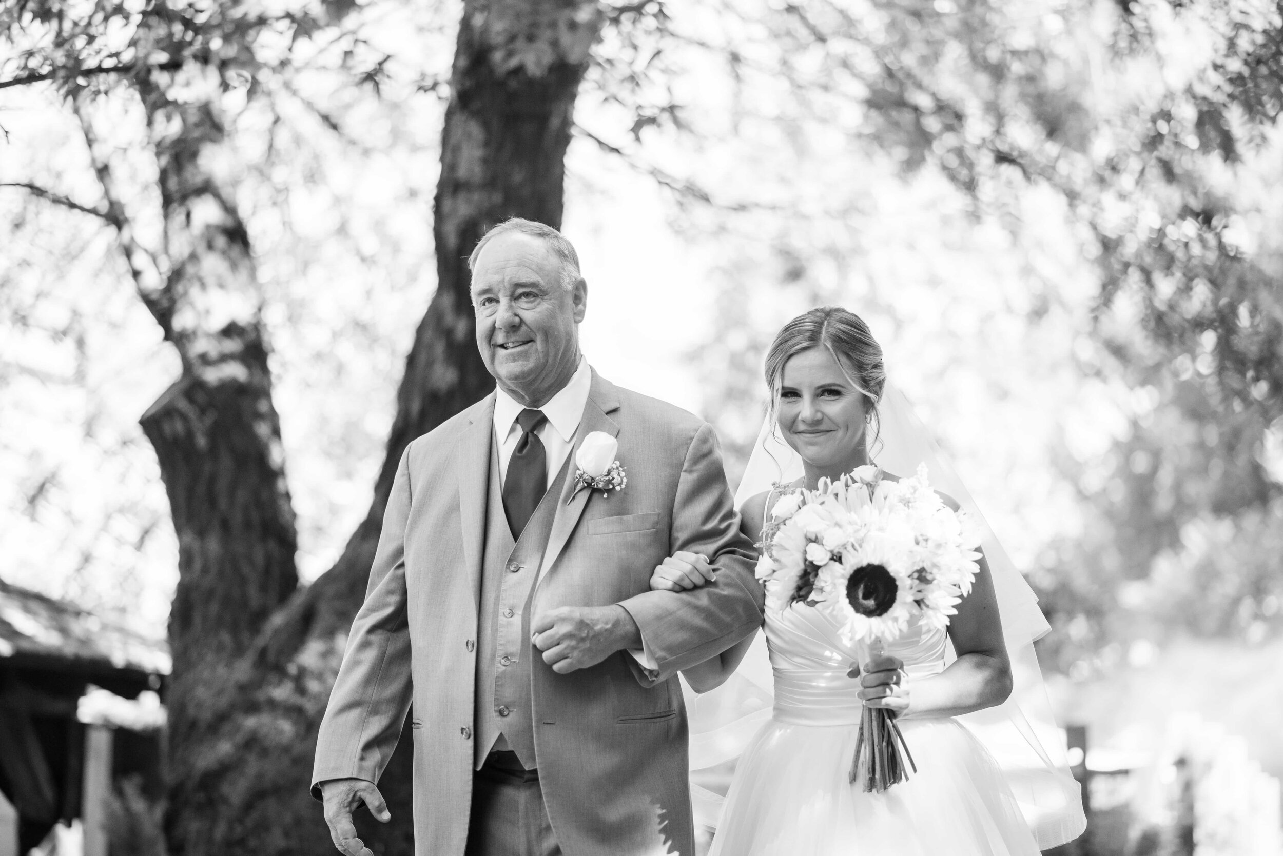 Black and white of bride and father walking to ceremony