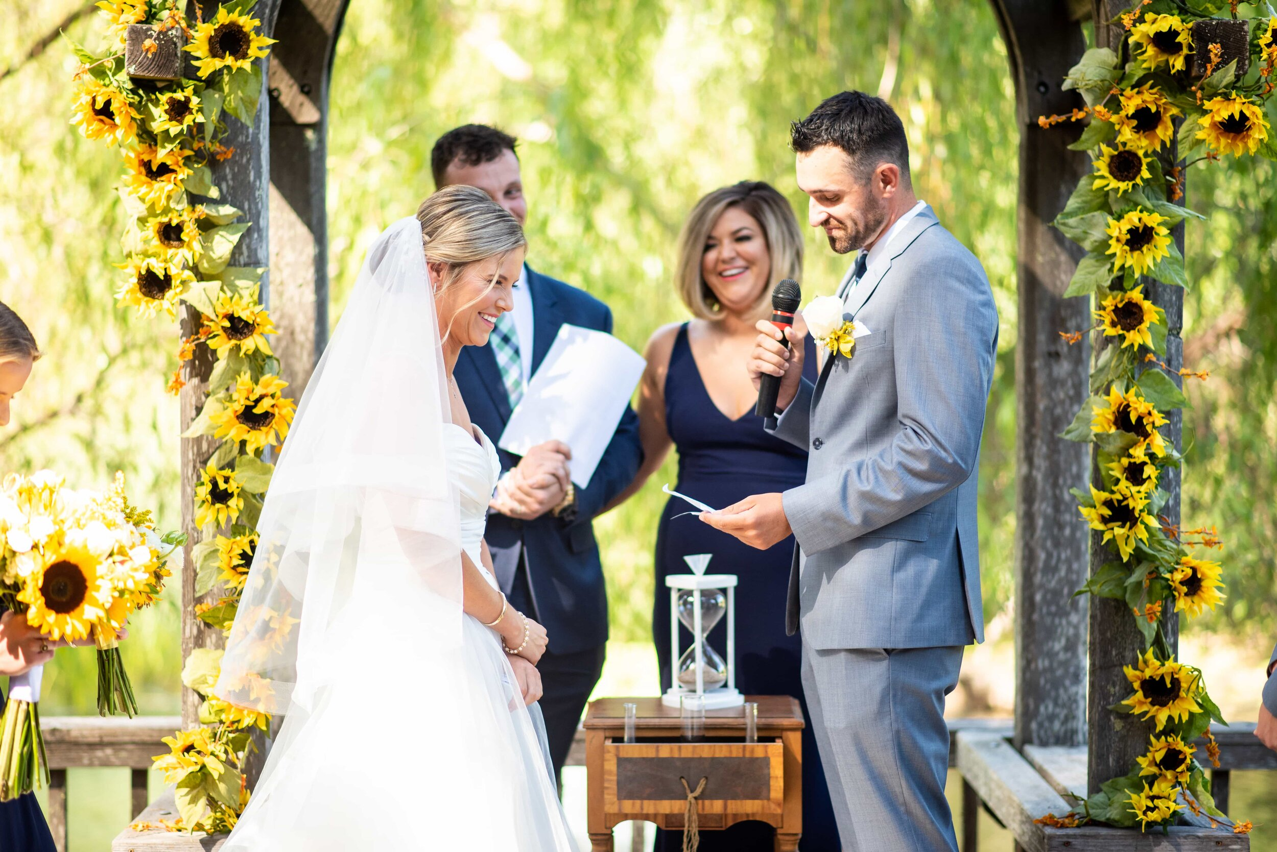 Bride and Groom in front of sunflower arch during ceremony