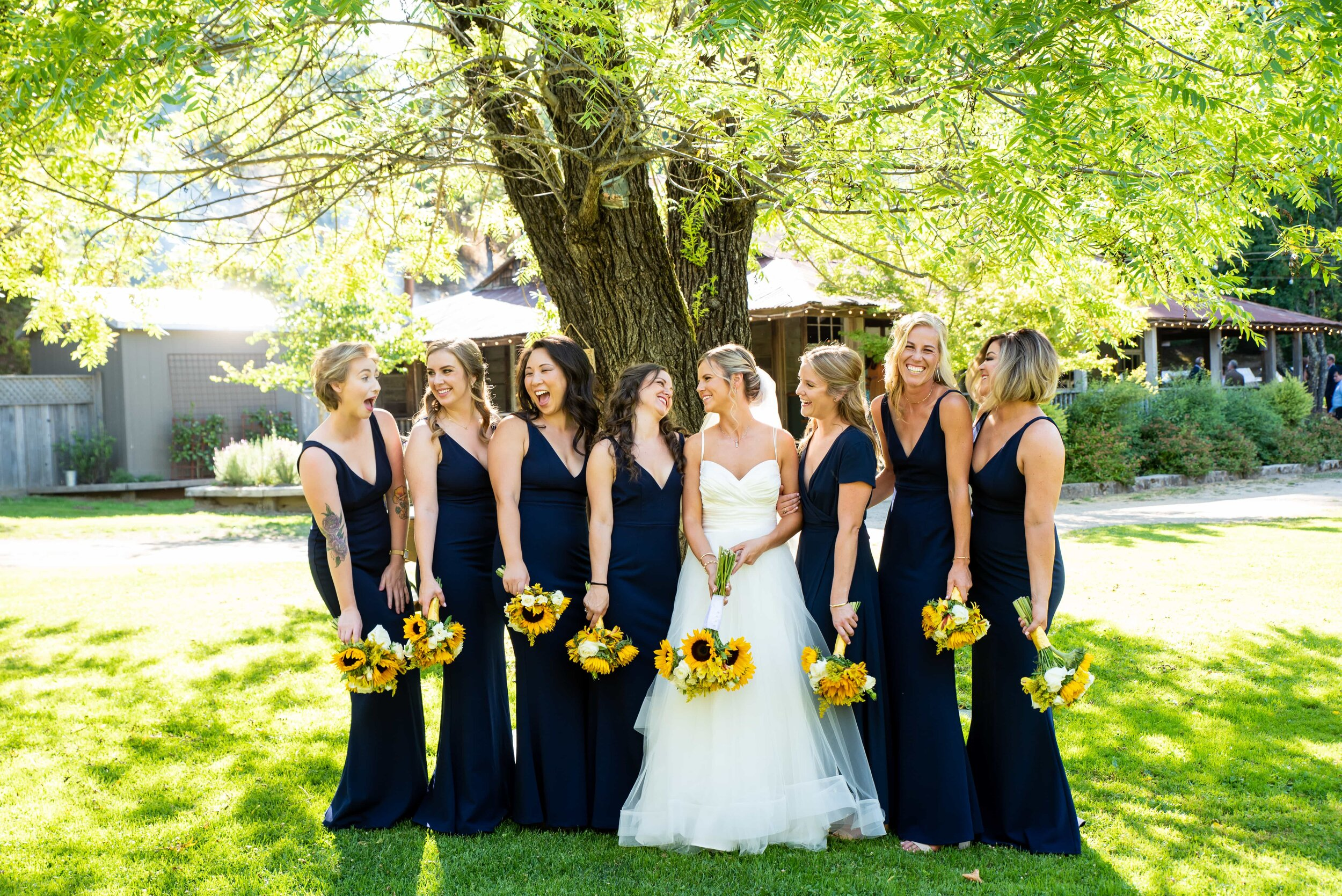 Candid of bridesmaids talking under willow tree