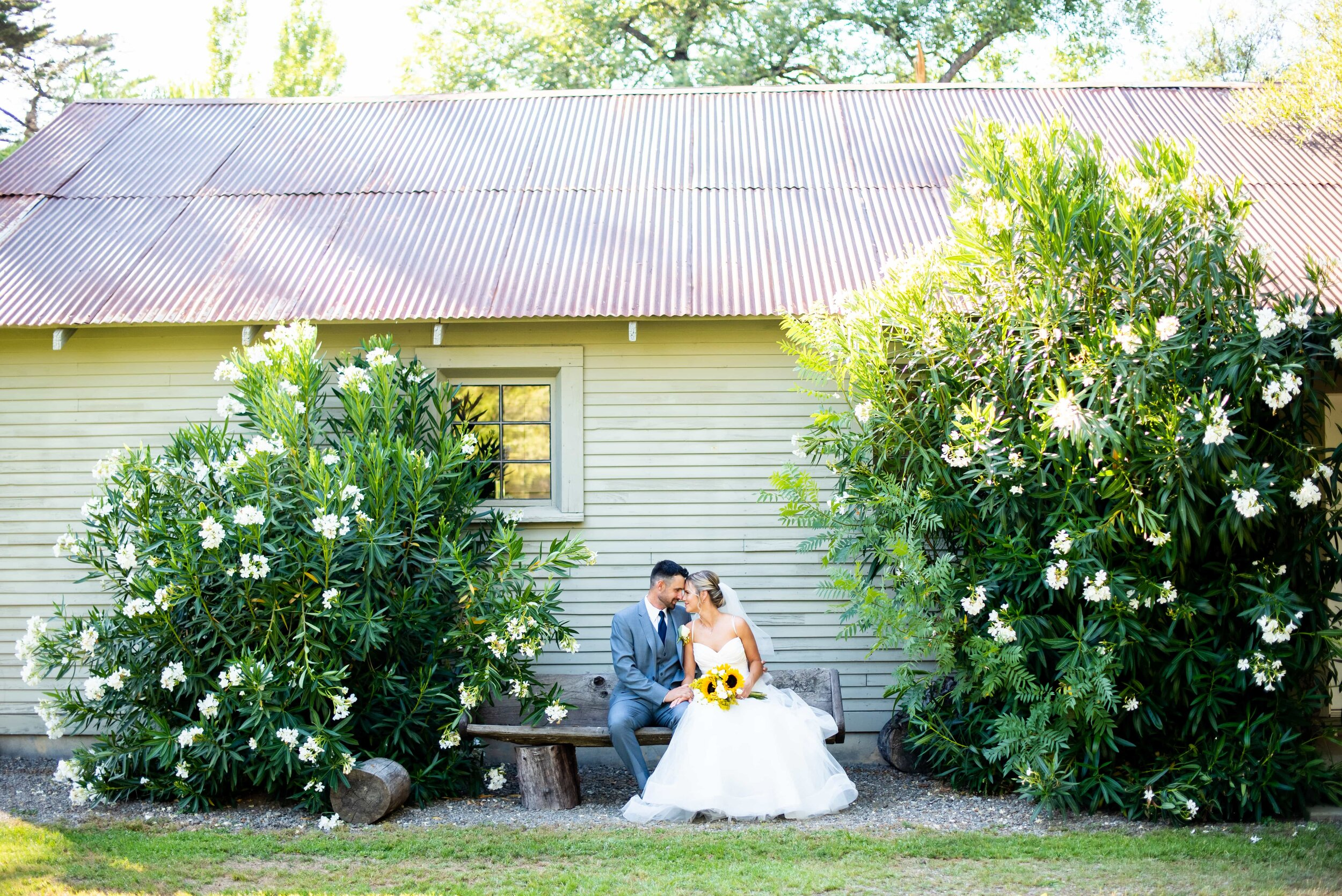 Bride and Groom on bench in front of barn